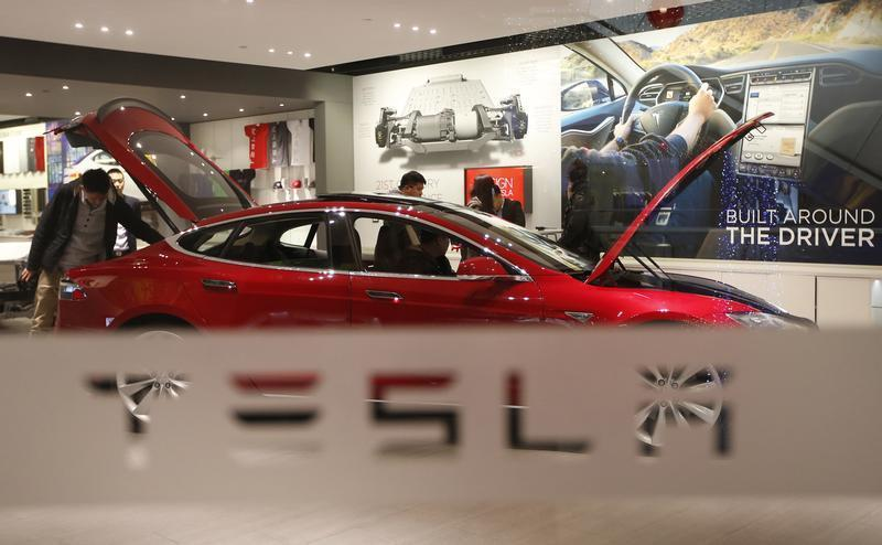 A man looks around Tesla Motors' Model S P85 at its showroom in Beijing